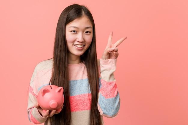 Jeune femme asiatique tenant une tirelire montrant le signe de la victoire et souriant largement.