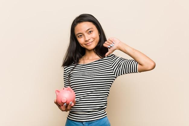Une jeune femme asiatique tenant une tirelire se sent fière et sûre d'elle, exemple à suivre.
