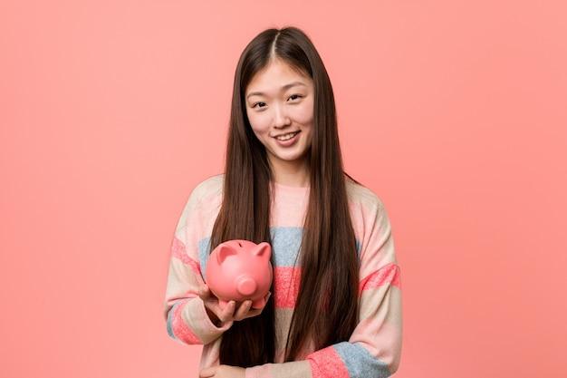 Jeune femme asiatique tenant une tirelire souriant confiant avec les bras croisés.