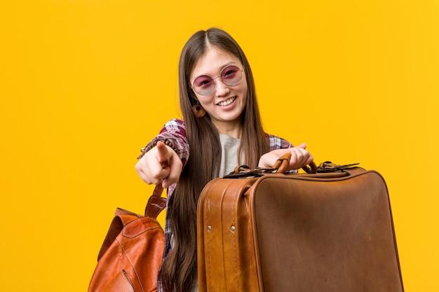 Jeune femme asiatique tenant une valise sourires joyeux pointant vers l'avant.