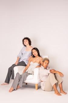 Jeune femme asiatique en tenue décontractée intelligente assise dans un fauteuil confortable en cuir blanc entourée de ses amis caucasiens et africains