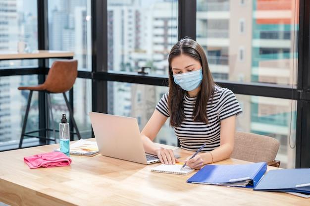Jeune femme asiatique en tenue décontractée avec masque facial et note de calendrier sur le calendrier au nouveau bureau normal