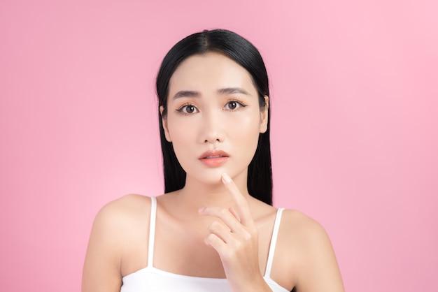Une jeune femme asiatique touche et s'inquiète pour son visage.