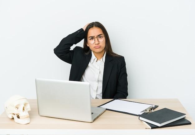 Jeune femme asiatique traumatologue isolée sur un mur blanc étant choquée, elle s'est souvenue d'une réunion importante