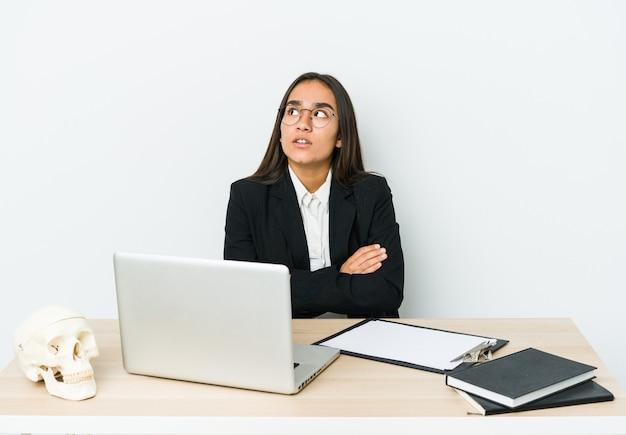 Jeune femme asiatique traumatologue isolée sur un mur blanc fatigué d'une tâche répétitive.