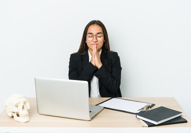 Jeune femme asiatique traumatologue isolée sur un mur blanc se tenant la main en priant près de la bouche, se sent confiant