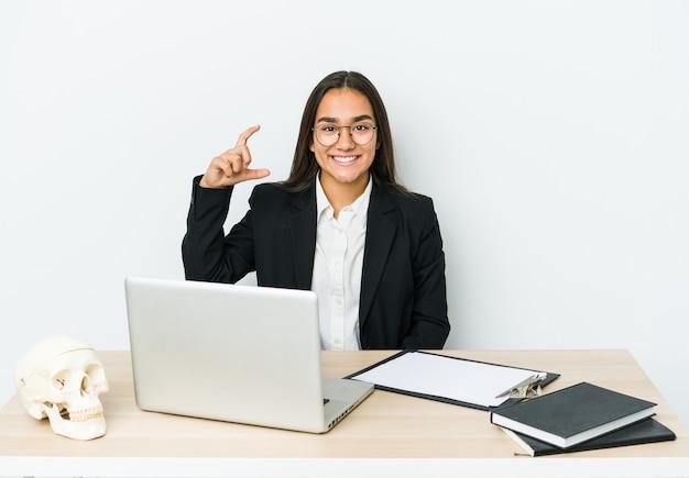 Jeune femme asiatique traumatologue isolée sur un mur blanc tenant quelque chose de peu avec l'index, souriant et confiant
