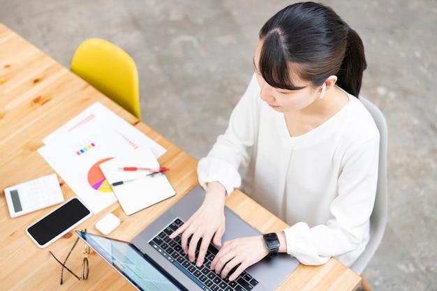 Jeune femme asiatique travaillant dans un espace décontracté