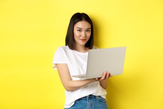 Jeune femme asiatique travaillant en freelance, utilisant un ordinateur portable et souriant, debout sur fond jaune.