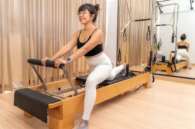 Jeune femme asiatique travaillant sur la machine de reformage de pilates pendant sa formation d'exercice de santé