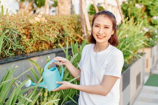 Jeune femme asiatique en tshirt blanc arrosant des plantes dans son jardin.