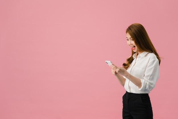 Jeune femme asiatique utilisant un téléphone avec une expression positive, sourit largement, vêtue de vêtements décontractés, se sentant heureuse et debout isolée sur fond rose.