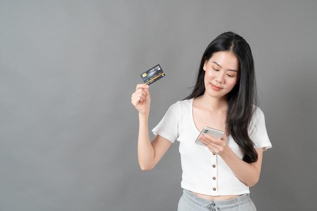 Jeune femme asiatique utilisant le téléphone avec la main tenant la carte de crédit - concept d'achat en ligne