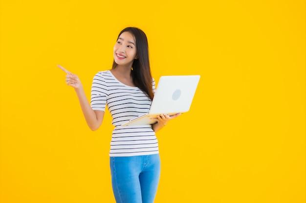 Jeune, femme asiatique, utilisation, ordinateur portable, ou, cahier