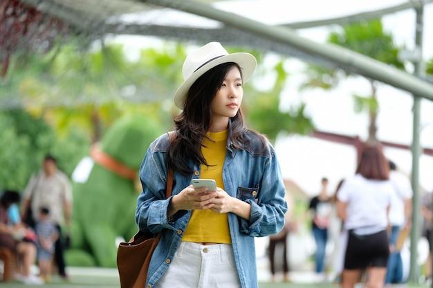 Jeune, femme asiatique, utilisation, téléphone intelligent, dans, dehors, ville, fond, gens, téléphone, style de vie