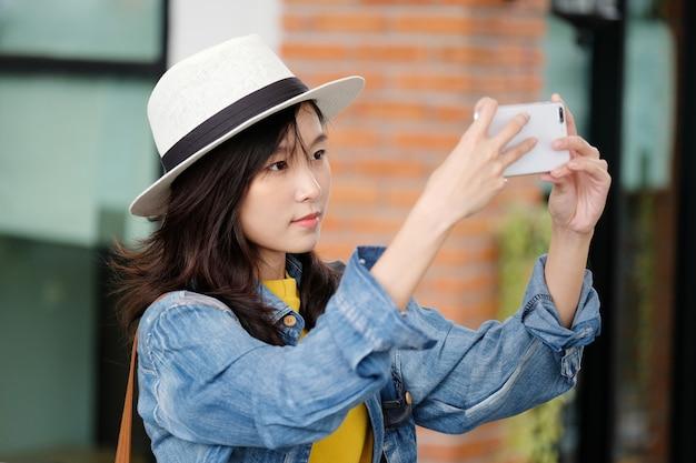 Jeune, femme asiatique, utilisation, téléphone intelligent, dans, ville, dehors, gens, dehors, à, technologie, gens, sur, téléphone, style de vie