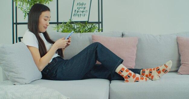 Jeune femme asiatique utilise un smartphone assis sur un canapé.