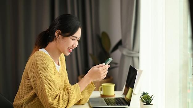 Une jeune femme asiatique utilise un téléphone mobile en surfant sur internet sans fil au bureau
