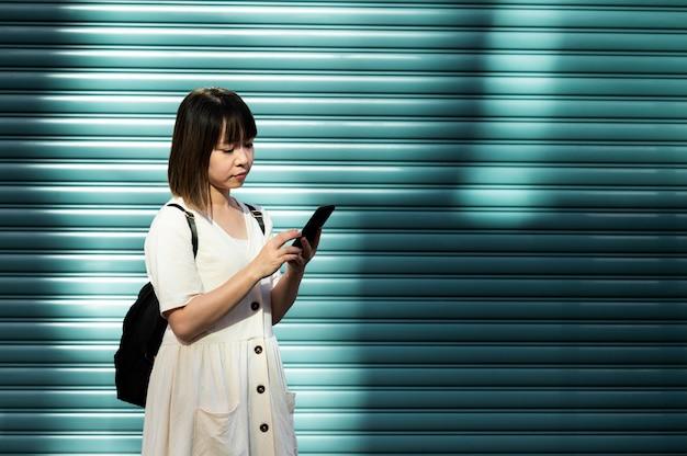 Jeune femme asiatique vérifiant son smartphone à l'extérieur