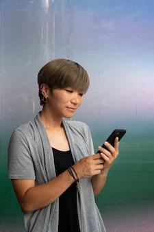 Jeune femme asiatique vérifiant son téléphone à l'extérieur