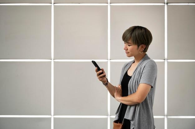 Jeune femme asiatique vérifiant son téléphone