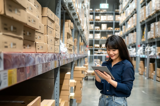 Une jeune femme asiatique vérificateur ou stagiaire travaille en levant les yeux et vérifie le nombre d'articles stockés par tablette numérique.