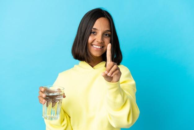Jeune femme asiatique avec un verre d'eau isolé sur bleu montrant et soulevant un doigt