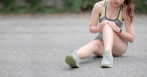Jeune femme asiatique en vêtements de sport assis sur le sol, ayant mal au genou en courant à l'extérieur dans le parc, copiez l'espace.
