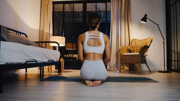 Jeune femme asiatique en vêtements de sport faisant des exercices de yoga dans le salon à la maison la nuit.