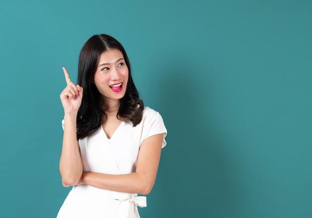 Jeune femme asiatique avec le visage de la pensée sur le bleu