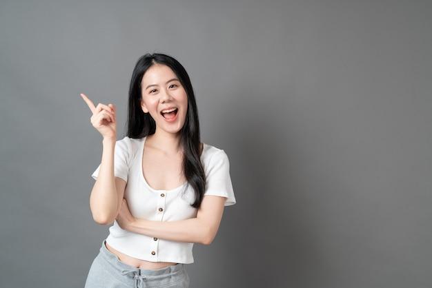 Jeune femme asiatique avec le visage de la pensée sur le mur gris