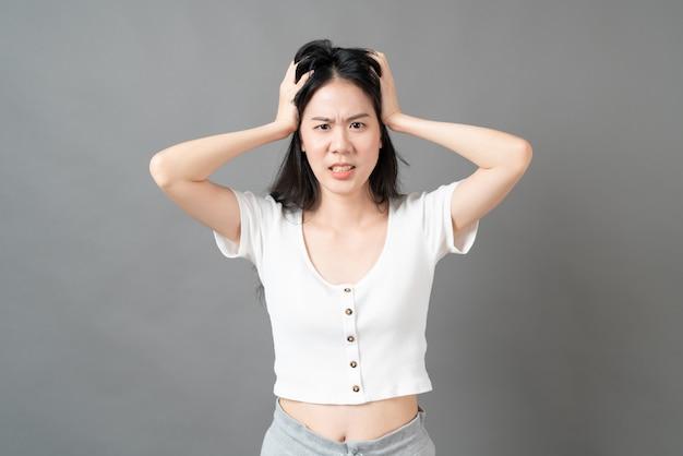 Jeune femme asiatique avec visage sérieux et souche en chemise blanche sur surface grise