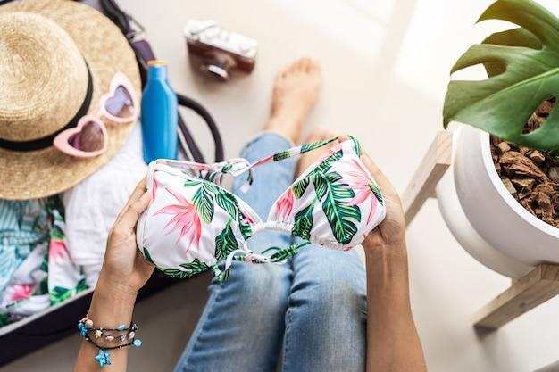 Jeune femme asiatique voyageur emballant sa valise et la planification des vacances d'été