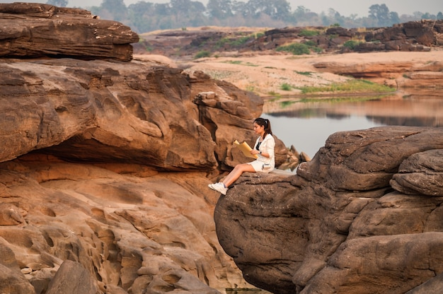 Jeune femme asiatique voyageur regardant carte papier sur la falaise rocheuse dans le grand canyon de la thaïlande