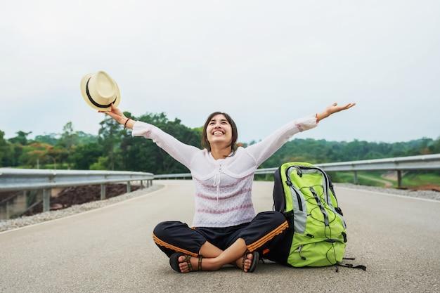 Jeune femme asiatique voyageur avec sac à dos relaxant assis sur la route