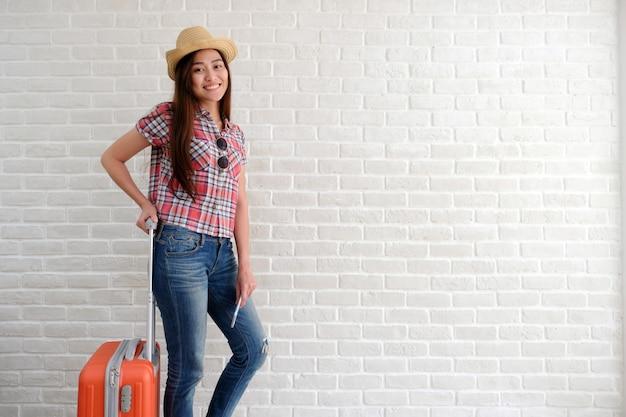 Jeune femme asiatique voyageur tenant le téléphone intelligent et les bagages dans la salle blanche.