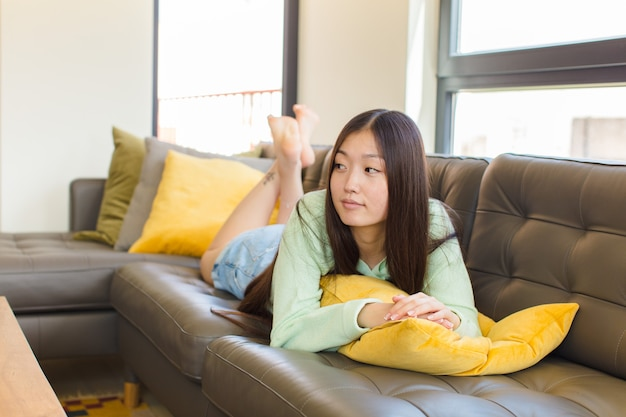 Jeune femme asiatique sur la vue de profil à la recherche de copier l'espace à venir, penser, imaginer ou rêver