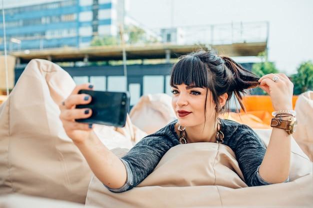 Jeune femme assez confiante, prendre une photo à l'extérieur dans une ville ou une ville urbaine. assis sur une chaise douce et prenez un selfie. posant seul et amusez-vous. vue urbaine.