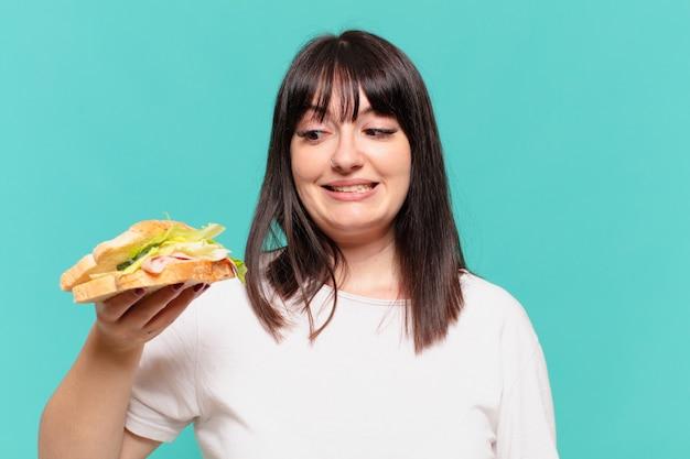 Jeune femme assez courbée doutant ou expression incertaine et tenant un sandwich