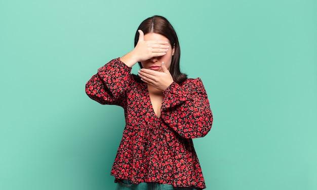 Jeune femme assez décontractée couvrant le visage avec les deux mains