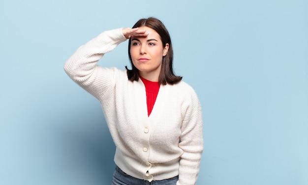 Jeune femme assez décontractée à la perplexité et étonné, avec la main sur le front à la recherche de loin, regarder ou chercher