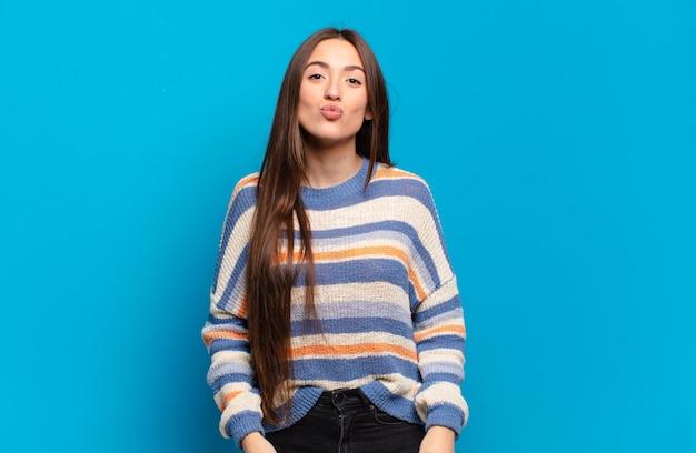 Jeune femme assez décontractée pressant les lèvres avec une expression mignonne, amusante, heureuse et charmante, envoyant un baiser