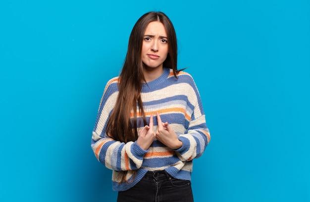 Jeune femme assez décontractée se montrant elle-même avec un regard confus et interrogateur, choquée et surprise d'être choisie