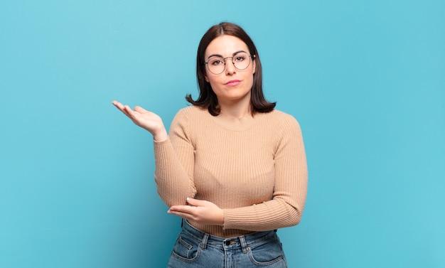 Jeune femme assez décontractée se sentant confuse et désemparée, s'interrogeant sur une explication ou une pensée douteuse