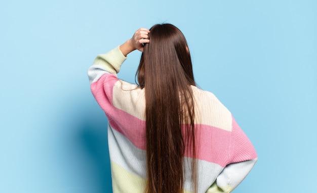 Jeune femme assez décontractée se sentant désemparée et confuse, pensant à une solution, avec la main sur la hanche et d'autres sur la tête, vue arrière