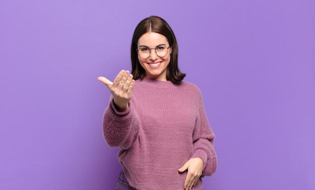 Jeune femme assez décontractée se sentant heureuse, réussie et confiante, faisant face à un défi et disant, allez-y! ou vous accueillir