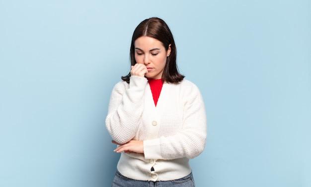 Jeune femme assez décontractée se sentant sérieuse, réfléchie et inquiète, regardant de côté avec la main pressée contre le menton