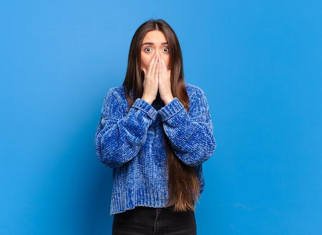 Jeune femme assez décontractée se sentir inquiet, bouleversé et effrayé, couvrant la bouche avec les mains, l'air anxieux et ayant foiré