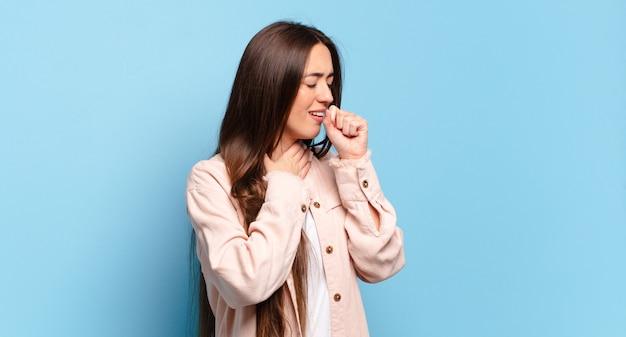 Jeune femme assez décontractée se sentir malade avec un mal de gorge et des symptômes de grippe, la toux avec la bouche couverte
