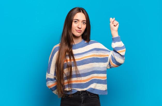 Jeune femme assez décontractée se sentir sérieuse, forte et rebelle, levant le poing, protestant ou luttant pour la révolution